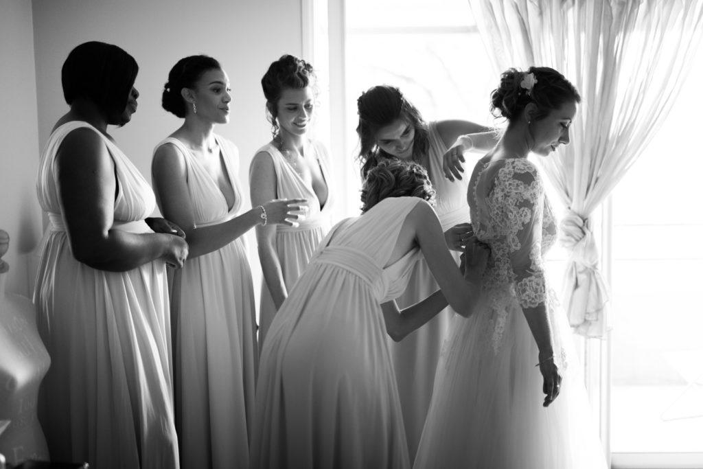 les témoins de la mariée l'aident à mettre sa robe pour son mariage au mas du lingousto à cuers