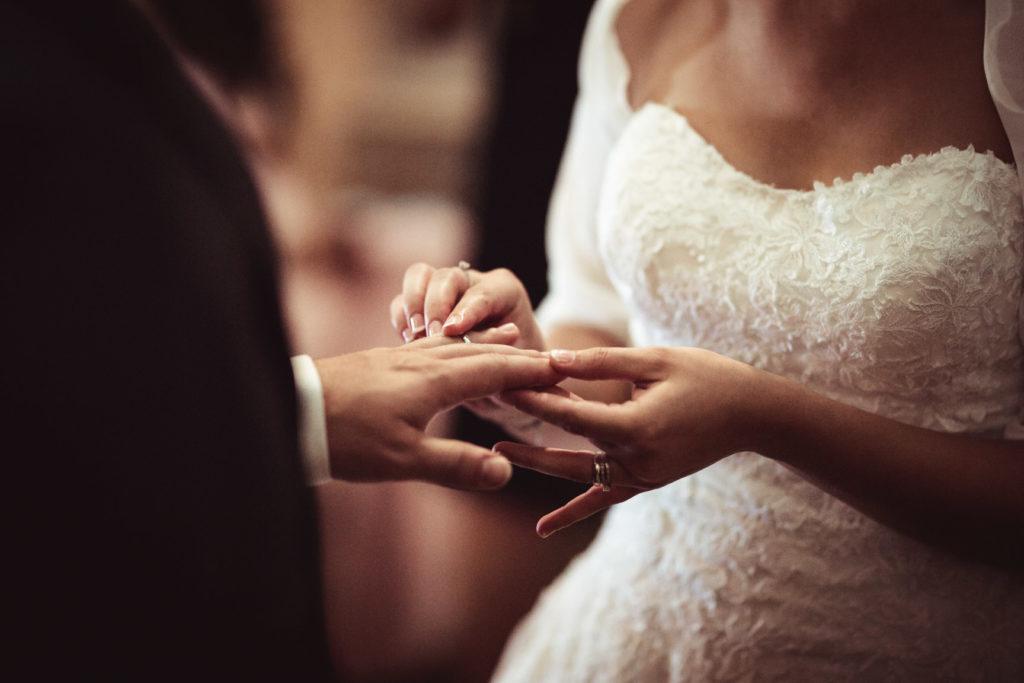 la mariée met la bague à son mari à l'église
