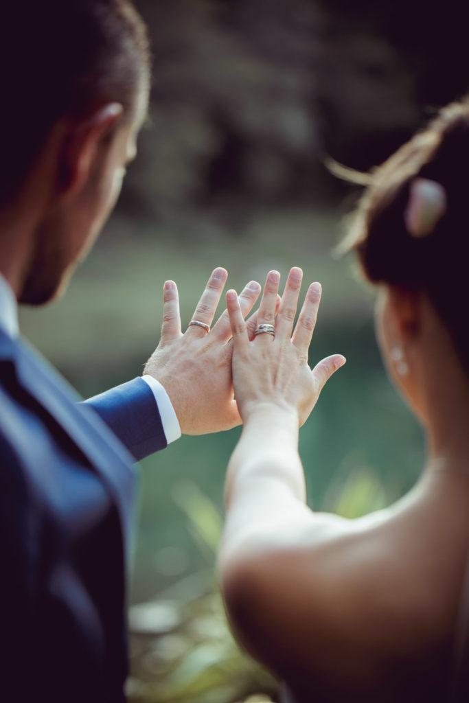 les mariés nous montrent leurs alliances au domaine de montrieux le vieux