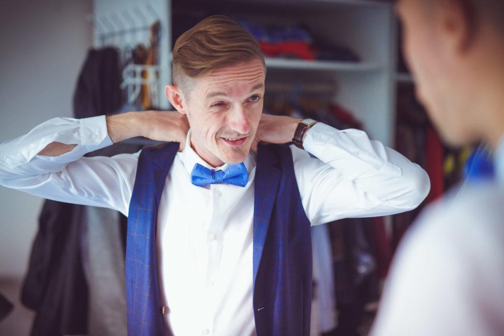 le marié enfile son costume avec son noeud papillon bleu