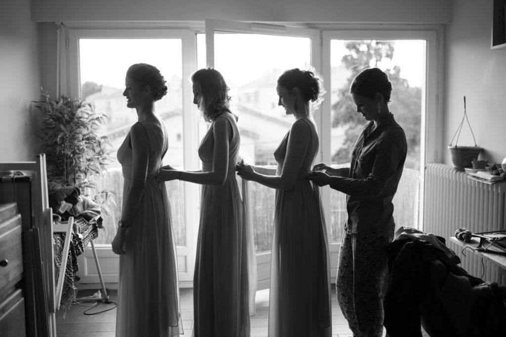 la mariée aide ses demoiselles d'honneur à s'habiller