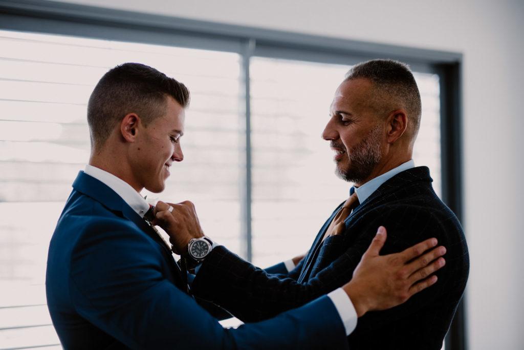 le père du marié aide son fils à mettre sa cravatte pour son mariage à Six-fours-les-plages enfile le costume pour son mariage à Six-fours-les-plages