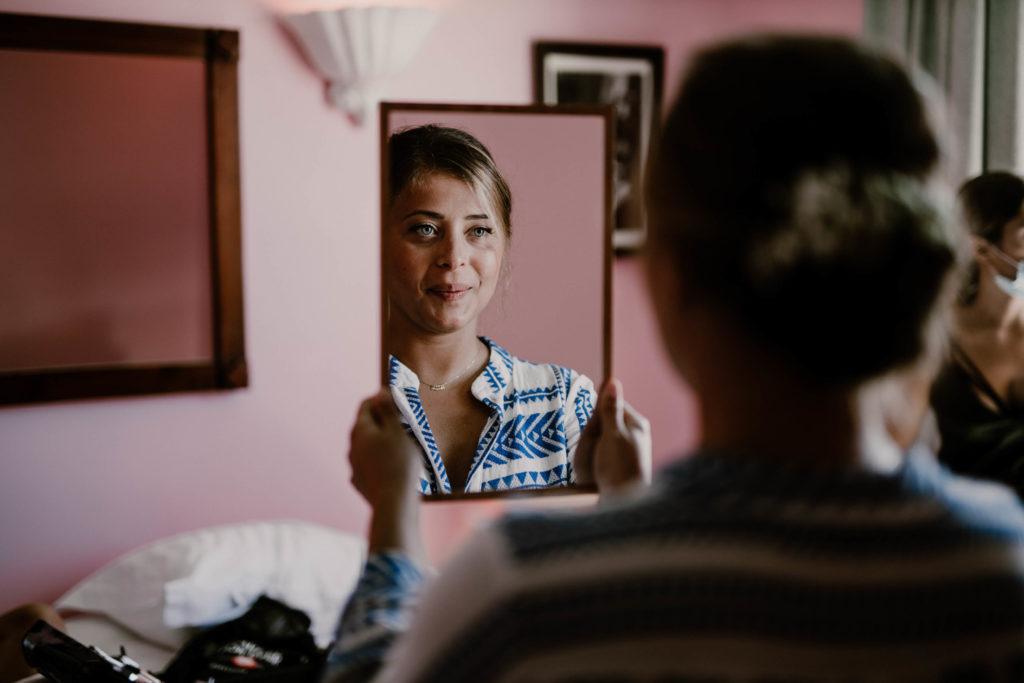 la mariée heureuse se regardfe dans son miroir pour son mariage à nice