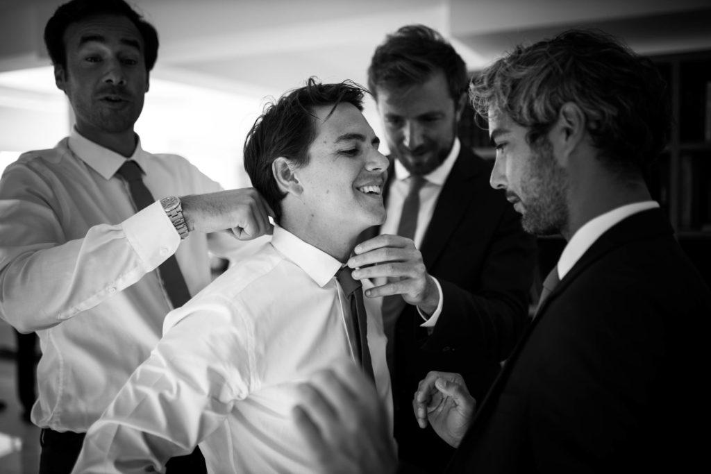 témoins de mariage qui aident le marié à mettre son costume